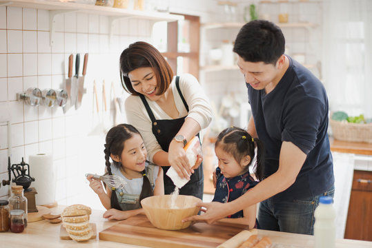 Young Asian love family are preparing the dough powder, cookies, cake on table in the kitchen which Excited smiling and felling happy. parent and daughter are cooking on the day at home.