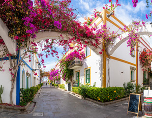 Street with blooming trees in Puerto de Mogan, Gran Canaria, Spain. Favorite vacation place for tourists and locals on island.