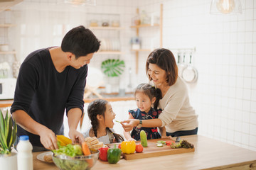 Young Asian love family are preparing the breakfast, sandwich vegetable on table in the kitchen which Excited smiling and felling happy. parent teach daughter to cooking food on the day at home.