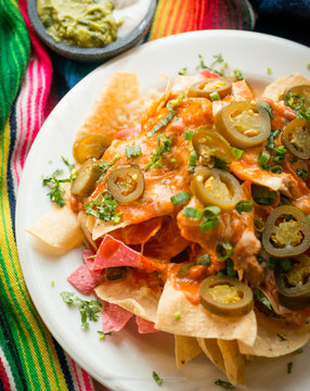 Nachos with melted cheese, beans, guacamole, sour cream, salsa, green onions, jalapeños, and enchilada sauce. Presented on a mexican sarape.
