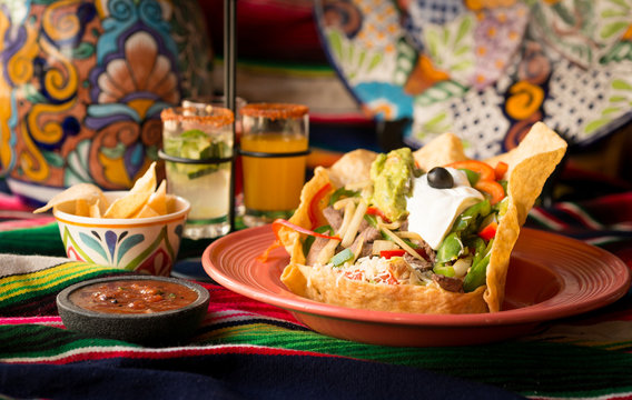 Crispy fajita tortilla tostada bowl with chicken, sautéed bell peppers, onions, tomato, topped with guacamole, sour cream, and olive. Served with chips and dipping salsa styled on a sarape.