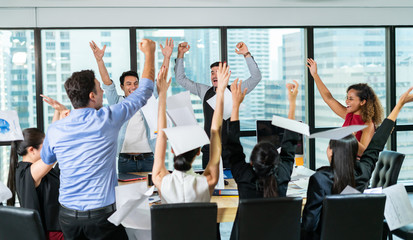 Multiethnic diverse Group of business people celebrating by throwing papers in the air and having fun in office.Happy business people cheering together,celebrate project success.