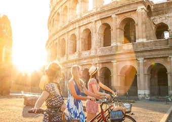 Printed kitchen splashbacks Rome Three happy young women friends tourists with bikes at Colosseum in Rome, Italy at sunrise.