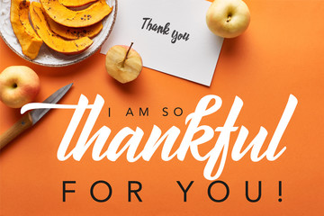 top view of pumpkin, apples, knife and thank you card on orange background with i am so thankful for you illustration