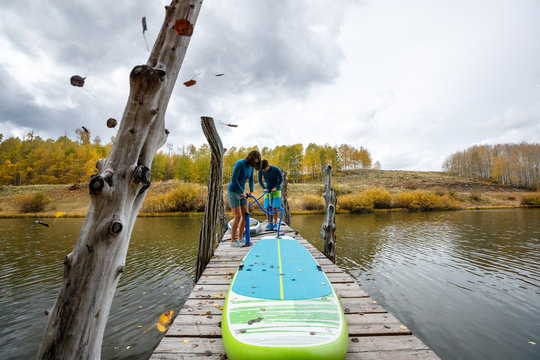 A man and a woman prepare their inflatable stand up paddle boards for SUPing in an alpine lake in the San Juan Mountains, Colorado in autumn.