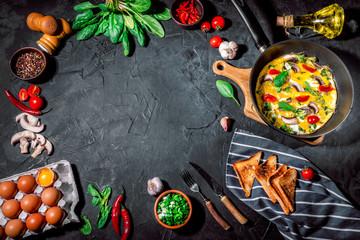 Keuken foto achterwand Eten Fresh homemade omelet with mushrooms, spinach and herbs on dark background
