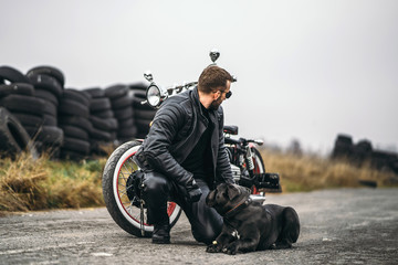 Biker in a leather suit crouched near his dog and red motorcycle on the road. Many tires on the...