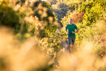 A young sportive man running some natural trails during the golden hour. Location: Rerik, northern Germany