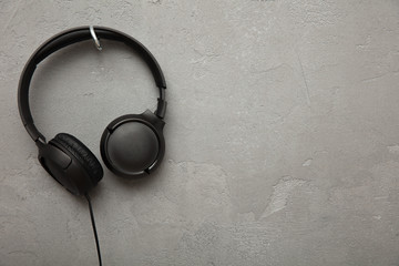 Headphones hangs on a hook on concrete background