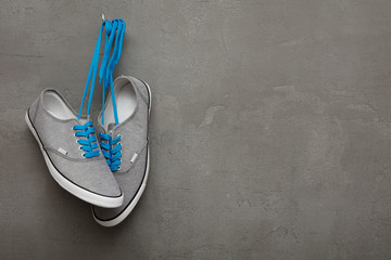 Grey sneakers with blue laces on concrete background