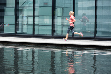 European Quarter, Stuttgart, Baden-W¸rttemberg, Germany: A female runner running along the glass walls of an office building that shows her reflection.