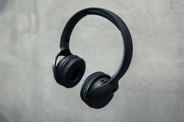 Headphones floates over concrete background