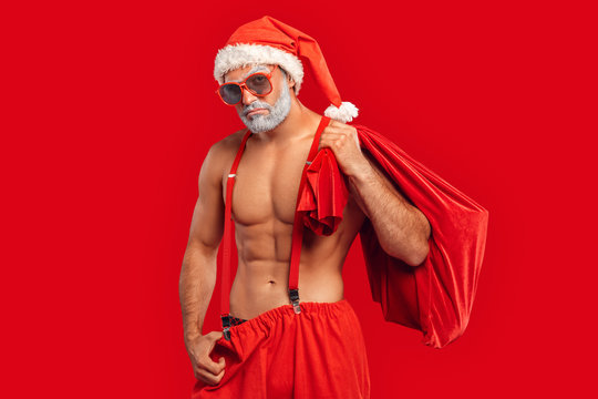 Adult sexy Santa Claus holding sack full of presents, making sad face