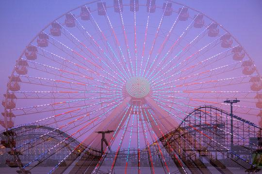 Amusement park rides, double exposure. Ferris wheel and roller coaster