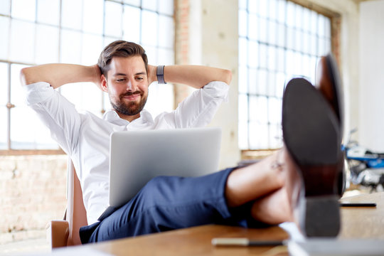 Young businessman with legs on the desk