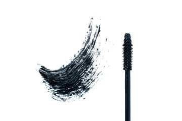 Black smear mascara and brush on white background. Trend concept. Isolated. Makeup. Cosmetic products for eyelashes. Photography. Top view. Beauty pattern. Beautiful template for design. Closeup