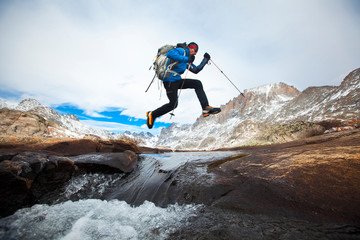 Hiker jumping across stream in Titcomb Basin