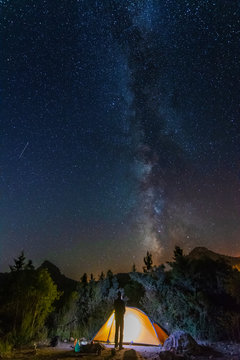 starry night with the Milky Way on the Turkish Mediterranean coast amidst the rocky mountains with tourists in a yellow tent