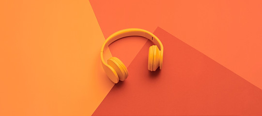 Minimal fashion, Trendy coral neon headphones. Music vibration on geometry background. Hipster DJ accessory Flat lay. Art creative summer vibes, fashionable pop art style. Bright neon color, banner