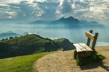 Wooden bench with beautiful views on Swiss Alps close to top of Mount Rigi