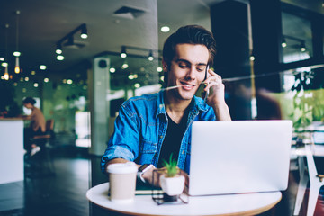 Smiling male student making positive telephone conversation while searching funny websites with...