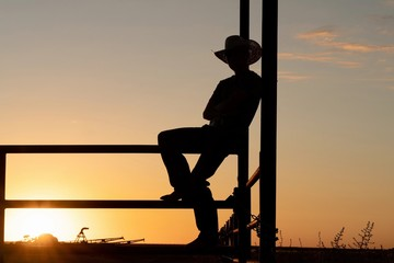 silhouette of cowboy on fence