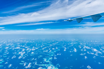 Aircraft wing flying over the blue clouds.