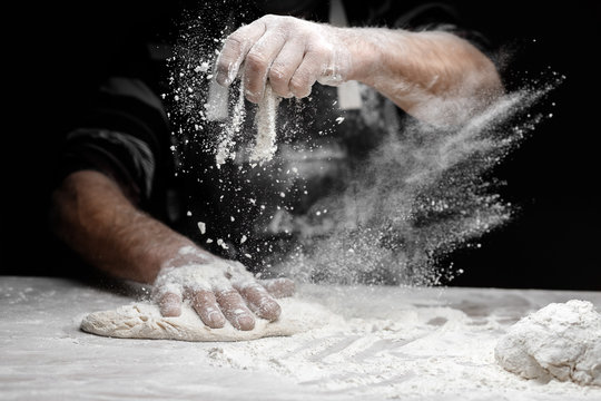 White flour flies in air on black background, pastry chef claps hands and prepares yeast dough for pizza pasta