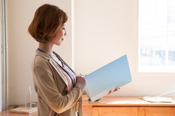 窓際に立ちファイルを確認する仕事中の20代女性