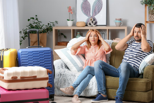 Stressed couple with packed suitcases at home