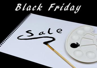 """Farbpalette mit schwarzer Acrylfarbe, Pinsel und Zeichenblock mit dem Text """"Black Friday und Sale"""""""