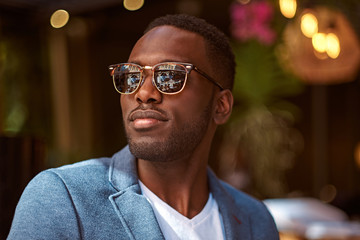 Portrait of young confident american businessman in sunglasses and blue blazer.