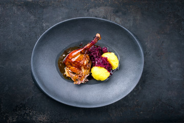 Traditional roasted Christmas duck leg with blue kraut and potato dumpling as top view on a modern design plate