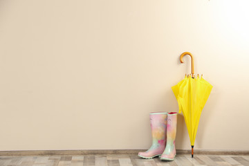 Wall Mural - Beautiful yellow umbrella and rubber boots near beige wall. Space for text