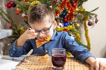 Obraz Chłopiec w okularach siedzi przy stole i ma buzię pełną jedzenia. Na talerzu leży lasagne a w tle pięknie ubrana choinka. Święta Bożego Narodzenia jedzenie. - fototapety do salonu