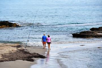 Couple walking along coastline