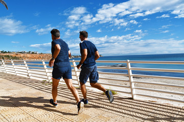 Torrevijeja, Spain - 11/13/2019 - Two young mans is running along tne beach