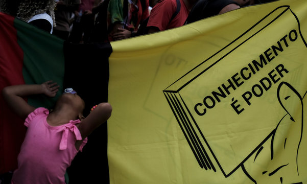 """Girl gestures next to a banner reading """"Knowledge is Power"""" as she marches accompanied by her parents during the National Black Consciousness Day in Sao Paulo"""