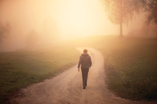 Man walking alone on morning rural misty road.