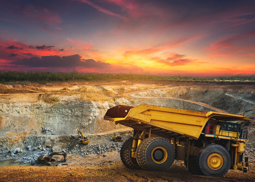 Yellow dump truck loading minerals copper, silver, gold, and other  at mining quarry.