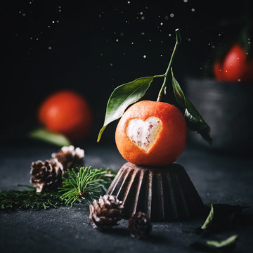 Sweet Tangerine with a cut out heart on dark mystic christmas background