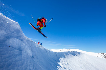 Wall Mural - A skier is riding and jumping at mountain terrain.