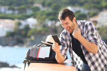 Excited tourist checking phone in a coast town
