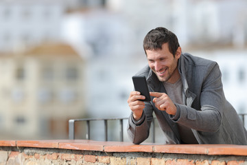Happy adult man in winter using mobile phone in a balcony