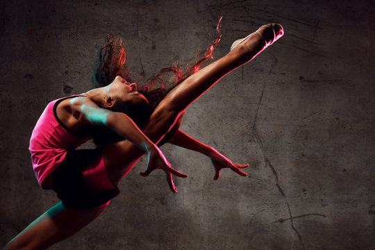 Street dance girl dancer jumping up dancing in neon light doing gymnastic exercises
