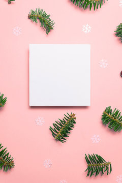 Blank card with fir tree branches and star confetti on pink background
