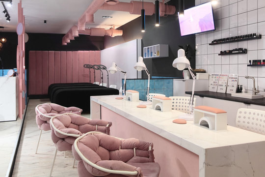Interior of luxury stylish beauty salon.First plan pink armchairs and table for manicure and second plan place for eyelash extension .Pink concept design.