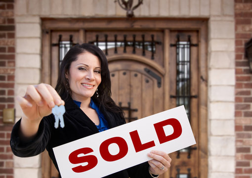 Hispanic Woman Holding Sold Sign and Keys In Front of House