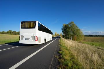 Fotobehang - White bus driving on asphalt road in autumn rural landscape