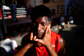 A boxer from Cuba has his faced lubed with vaseline prior to a friendly match against Uzbekistan in Havana